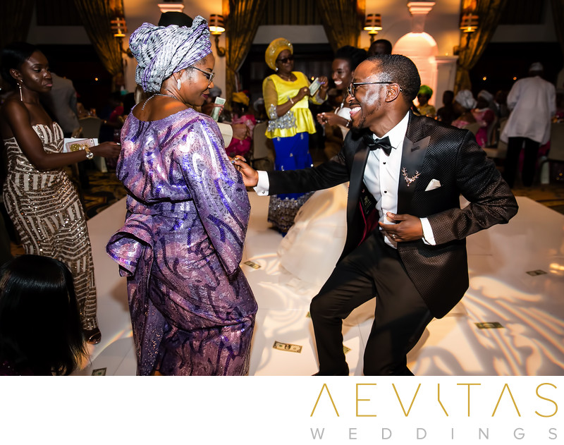 Action shot of mother-son dance at Nigerian wedding