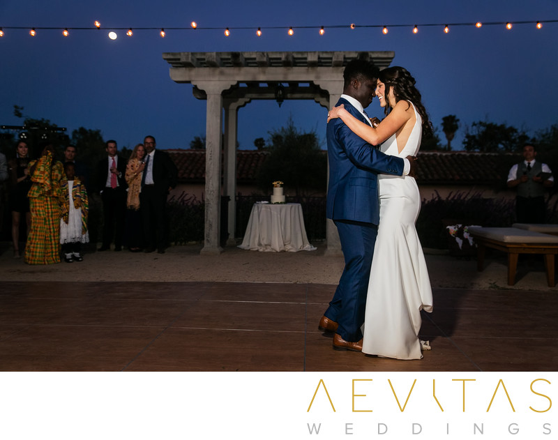 Couple first dance beneath courtyard string lights