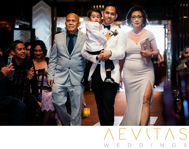 Groom and son walk down aisle with parents