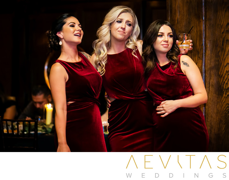 Candid photo of bridesmaids in red velvet dresses