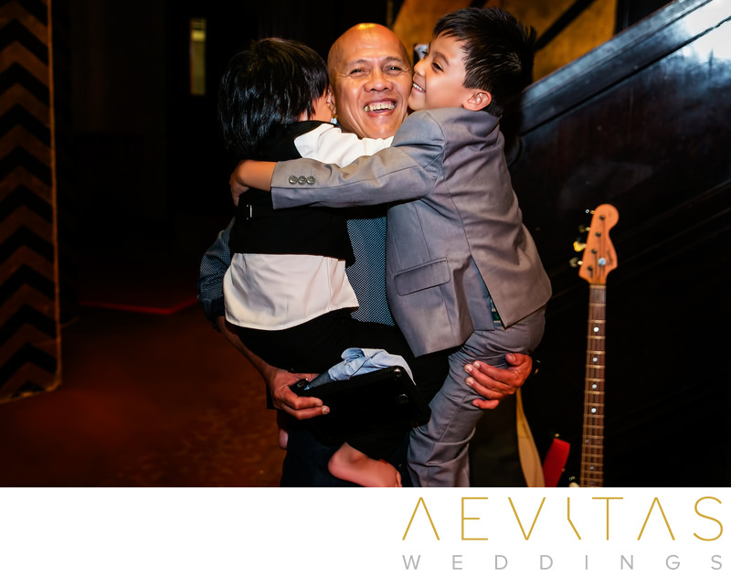 Young wedding guests hug grandpa in Los Angeles