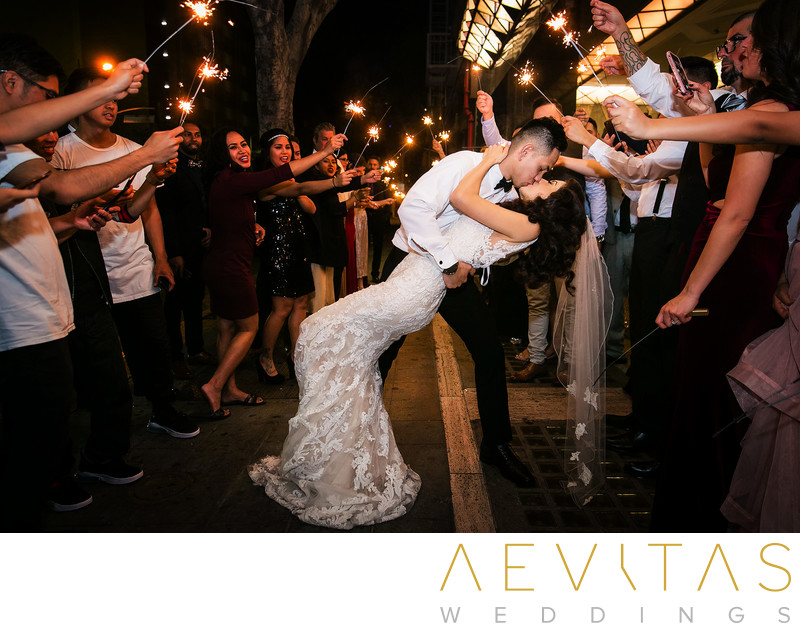 Groom dips and kisses bride during grand sparkler exit