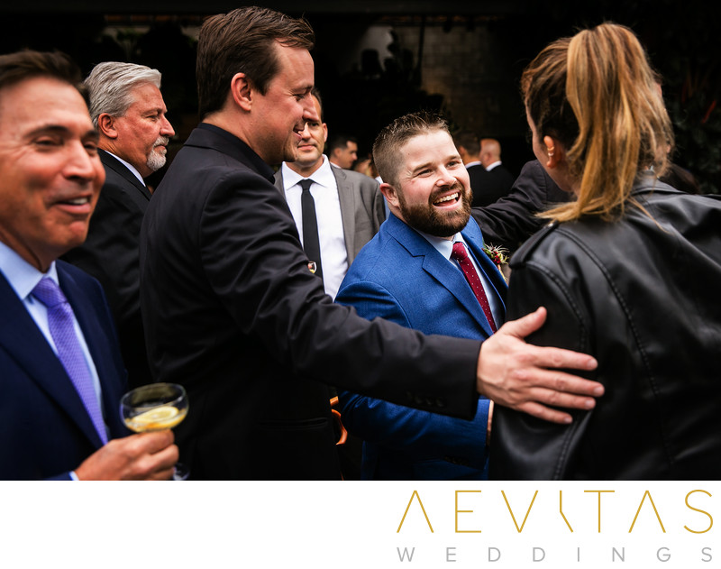 Candid moment between groom and wedding guests in LA