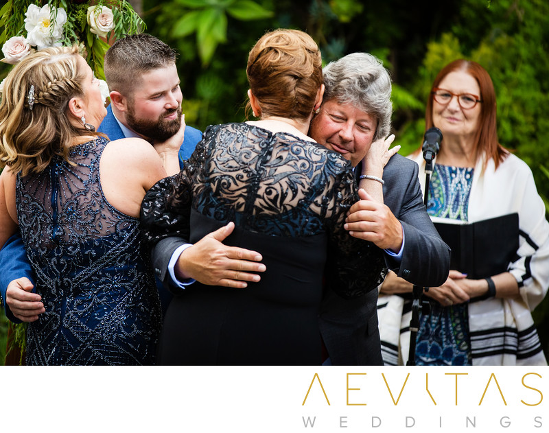 Parents of bride and groom embrace at LA wedding