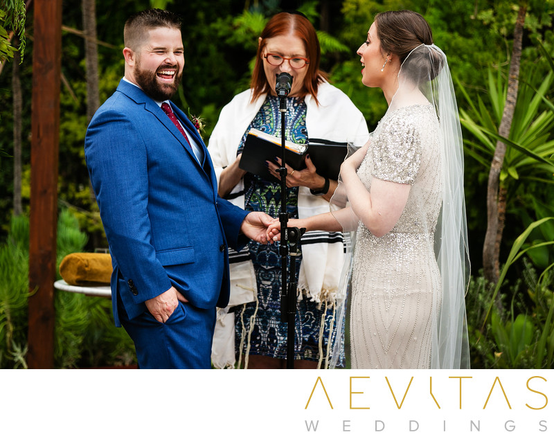 Groom laughs during intimate courtyard wedding ceremony