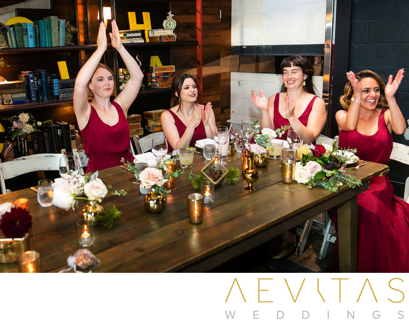 Bridesmaids in red dresses clapping at reception