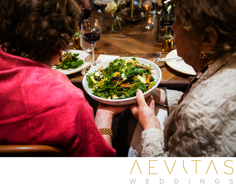 Wedding guests pass salad at SmogShoppe reception