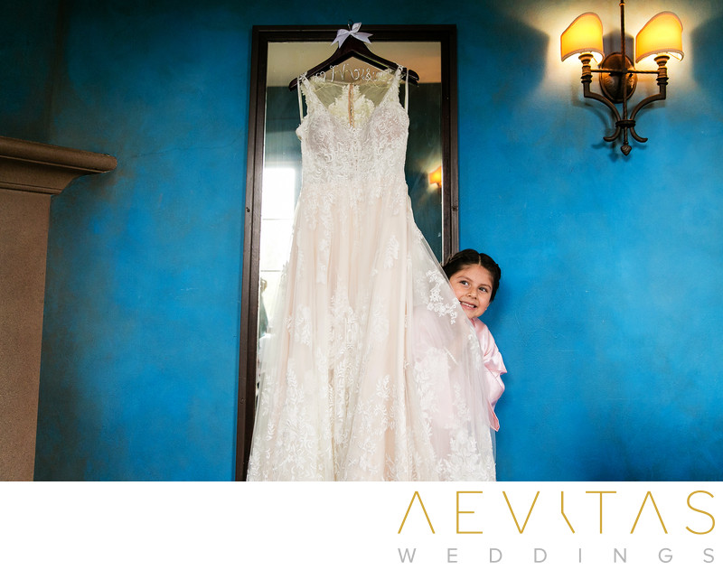 Flower girl hiding behind wedding dress Villa Del Sol