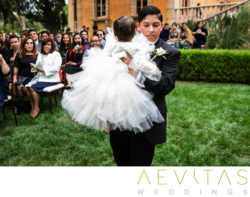 Flower girl being carried down grassy ceremony aisle