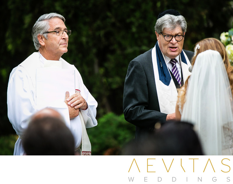 Candid photo of Priest and Rabbi at wedding ceremony