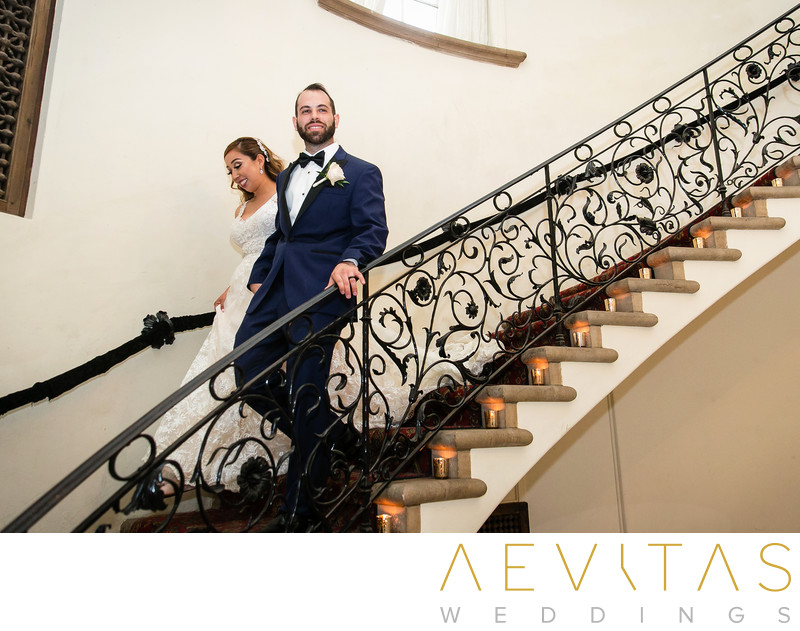 Bride and groom walk down wrought iron staircase