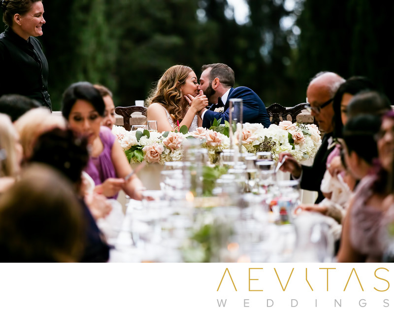 Creative couple kiss at sweetheart table