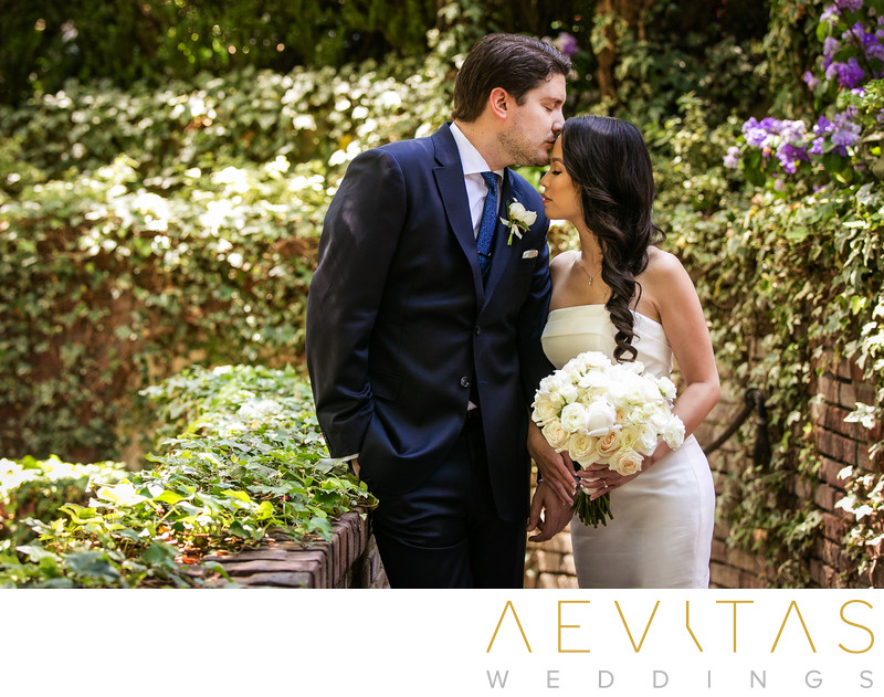 Groom kisses bride's forehead at The Houdini Estate