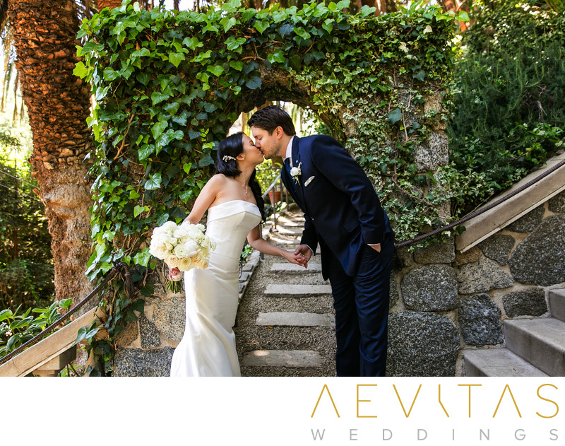 Couple kiss at ivy-covered garden archway in LA