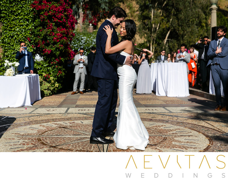 Bride and groom dancing on mosaic courtyard