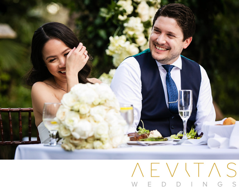 Candid couple laughing at sweetheart table in LA