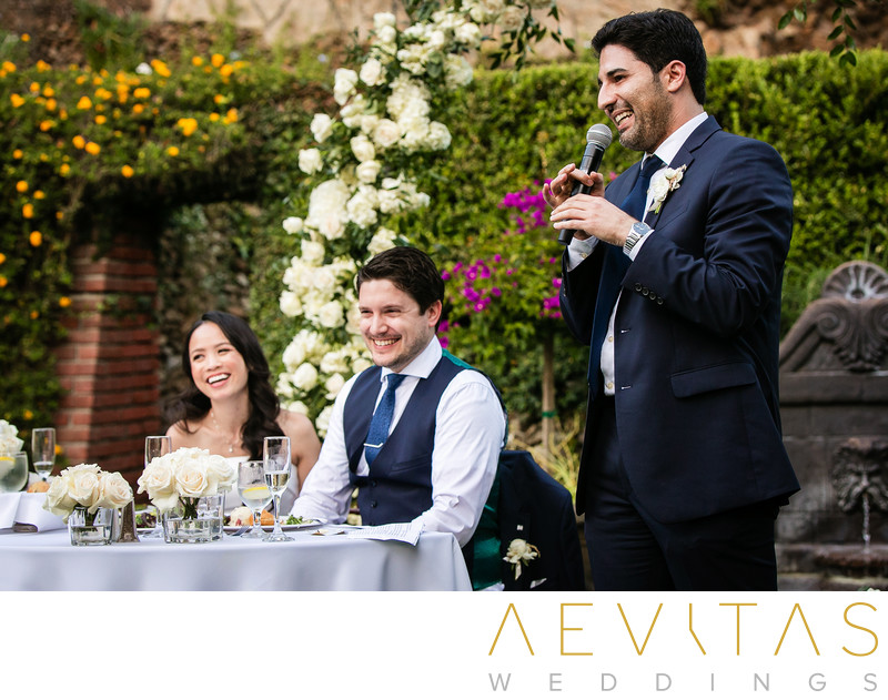 Groomsman toast with couple at sweetheart table