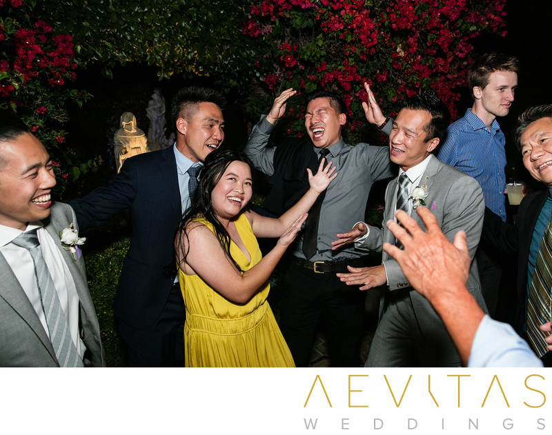 Wedding guests singing on dance floor candid photo