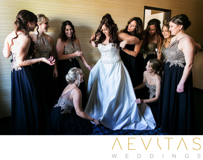 Bride getting into dress with bridesmaids Anaheim Hills
