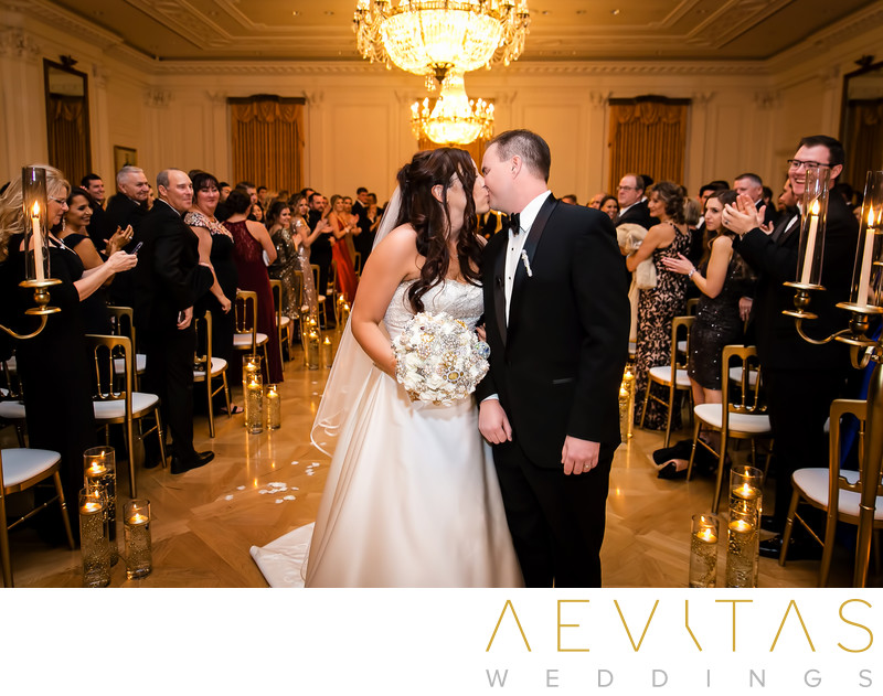 Couple kiss beneath chandelier at ballroom ceremony