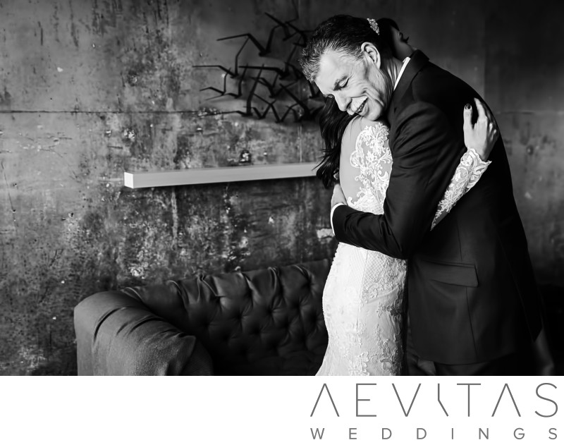 Black and white bride and father embrace at LA wedding