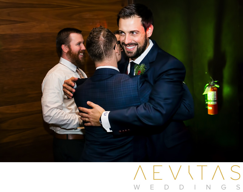 Groom embraces groomsman at Tiato wedding reception