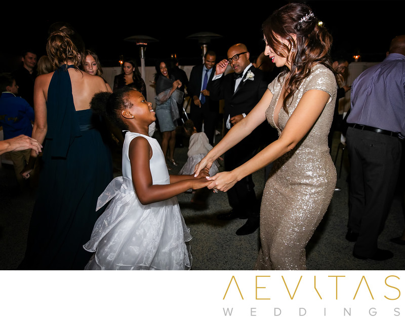 Bride and flower girl dancing at Santa Monica reception