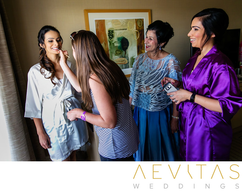 Bride having makeup applied with mom and sister Irvine