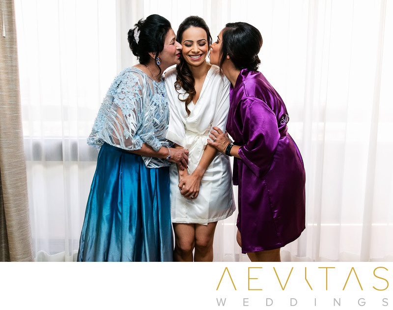 Bride being kissed by mom and sister at Hotel Irvine