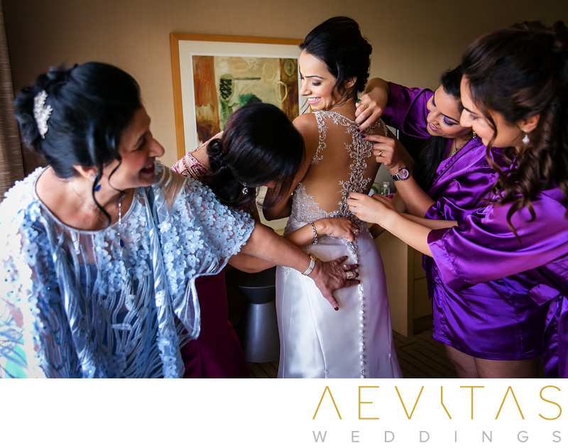 Bridesmaids doing up bride's dress Hotel Irvine suite