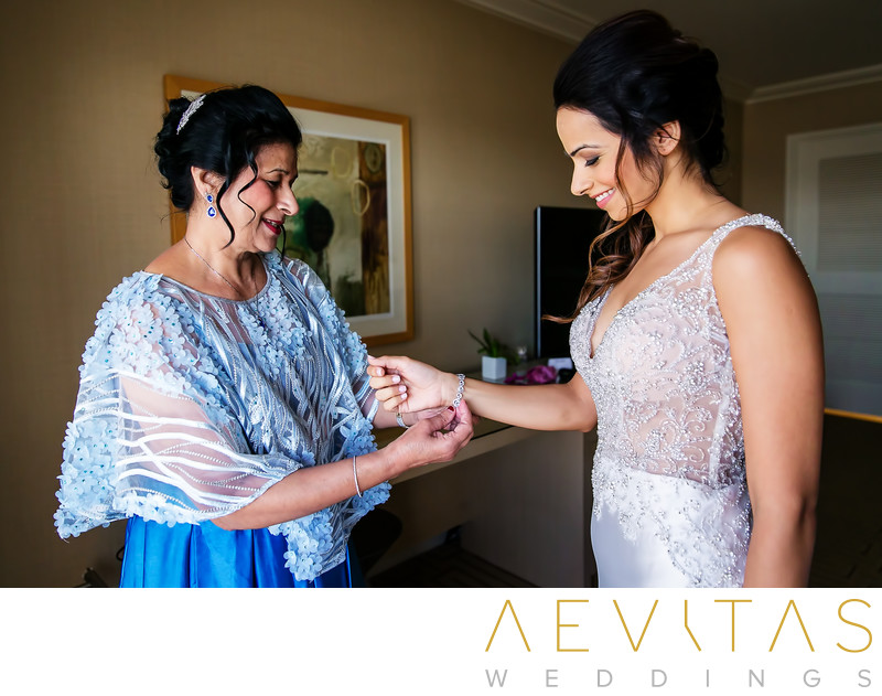 Mom securing bride's bracelet in Hotel Irvine suite