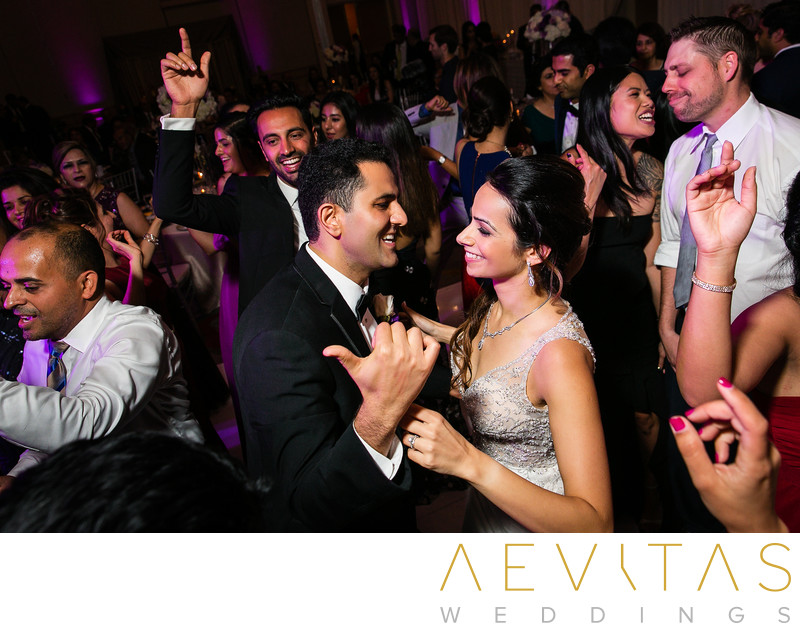 Couple dancing surrounded by guests at Persian wedding
