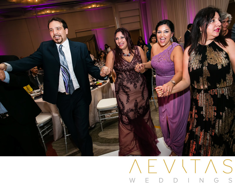 Wedding guests holding hands on dance floor in Irvine
