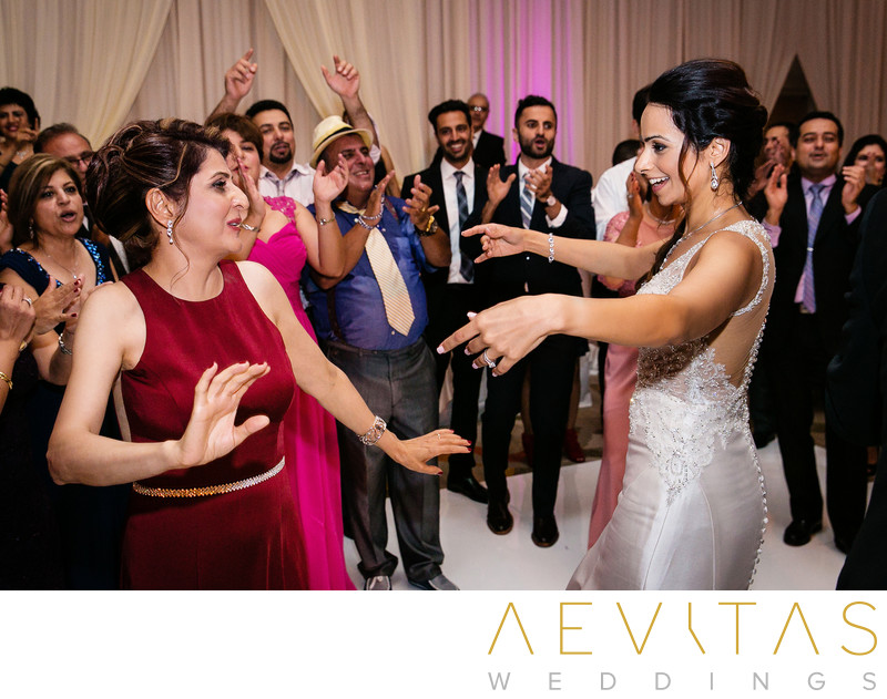 Bride and mother-in-law dancing at Persian wedding