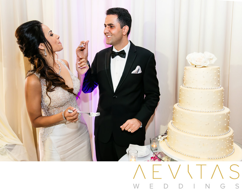Groom feeds bride cake Hotel Irvine wedding reception