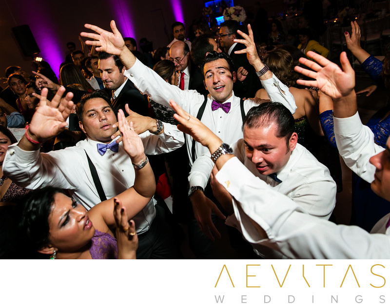 Groomsmen dancing with hands in air at Hotel Irvine