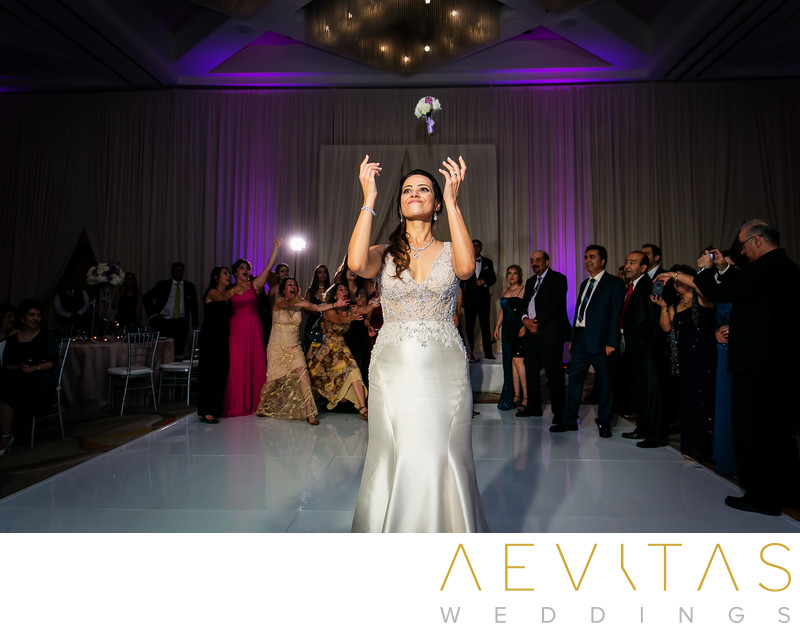 Action shot of bride's bouquet toss at Hotel Irvine