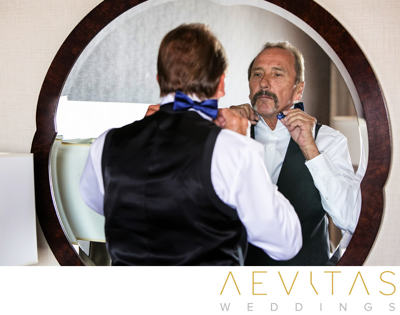 Reflective father tying bowtie in hotel suite mirror