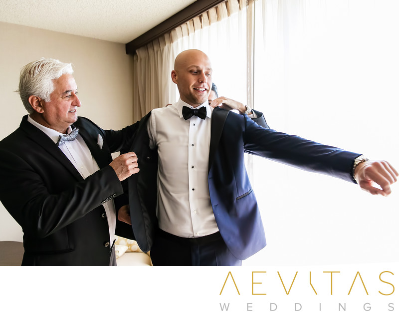 Groom putting on jacket at Hilton Sacramento Arden West