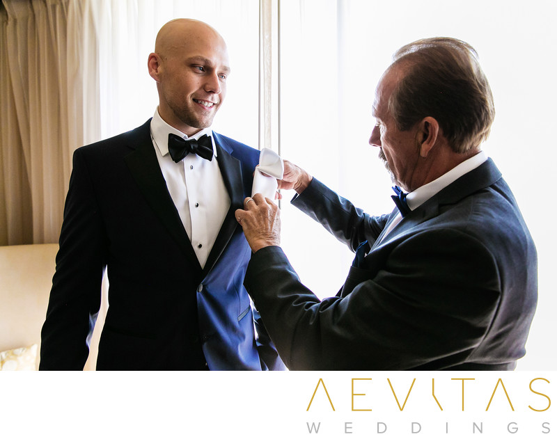 Father helping groom with boutonniere in Sacramento