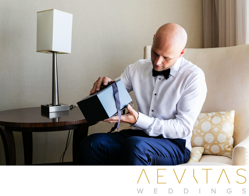 Groom opening gift at Hilton Sacramento Arden West