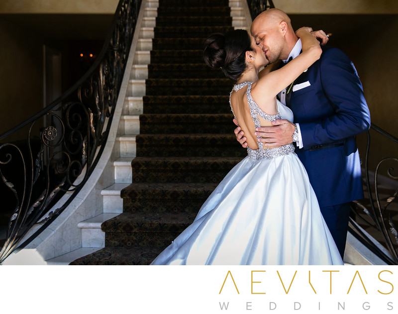 Couple kiss with staircase at Arden Hills Resort Club