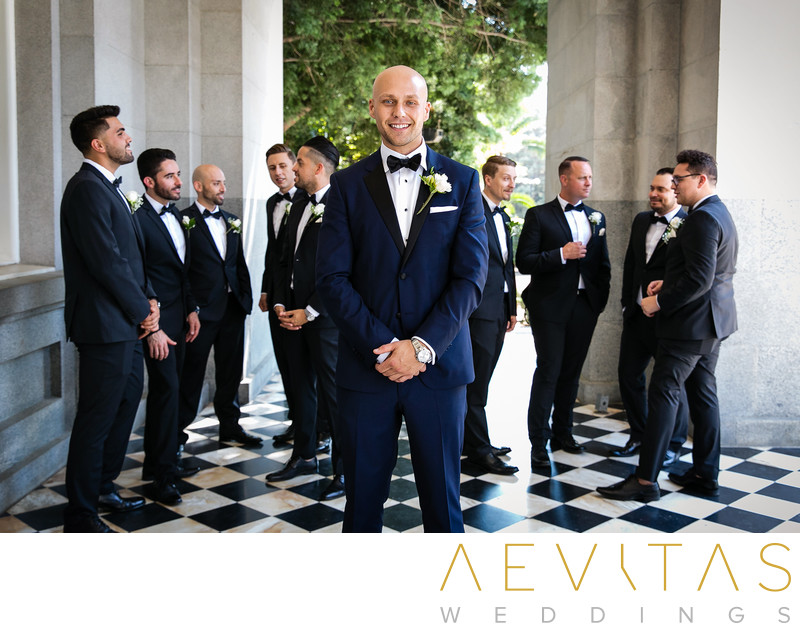 Creative portrait of groom with groomsmen behind