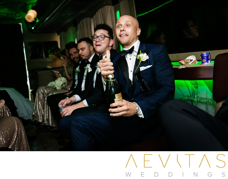 Candid photo of groom popping champagne bottle
