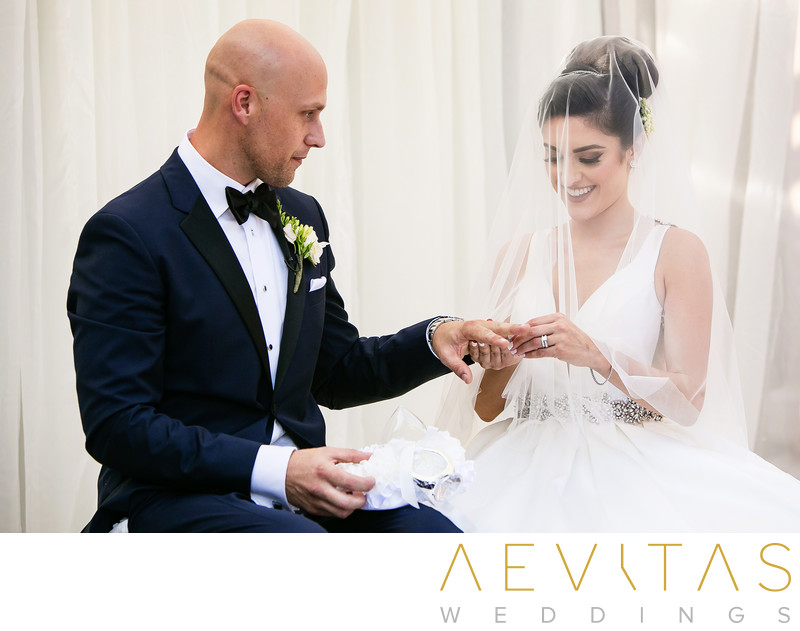 Bride puts ring on groom at Sacramento wedding ceremony