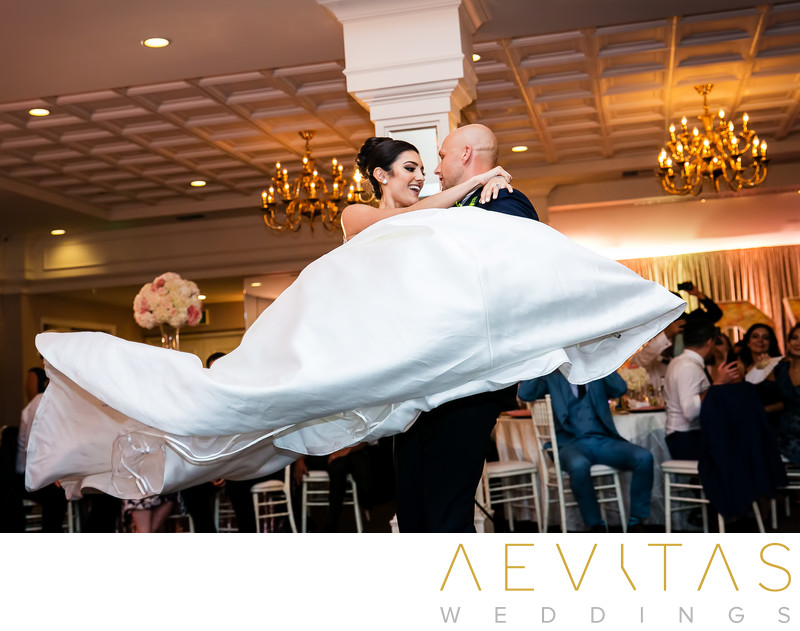 Groom spins bride during ballroom first dance