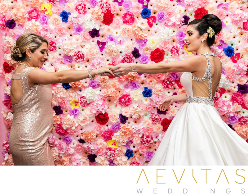 Bride and bridesmaid dancing with floral reception wall