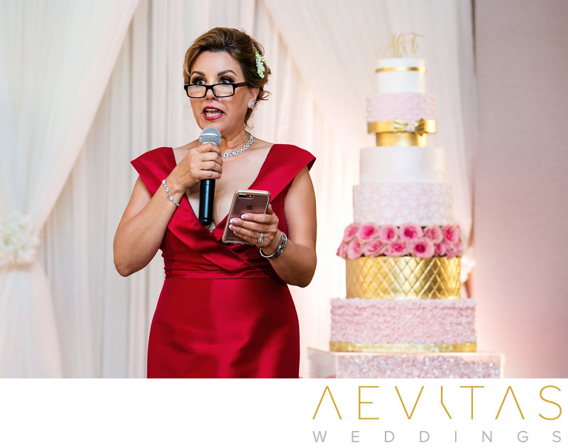 Woman in red speech with multi-tiered wedding cake