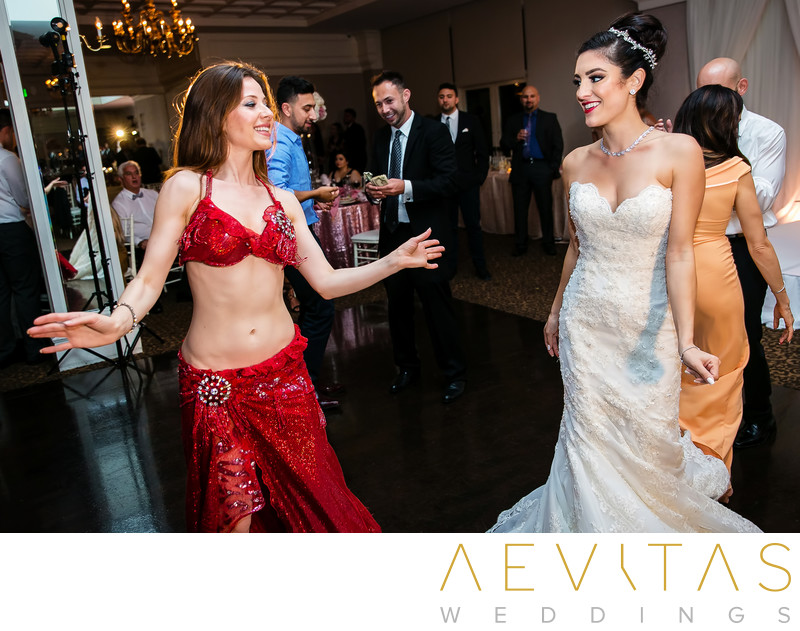 Candid moment bride and Persian wedding dancer
