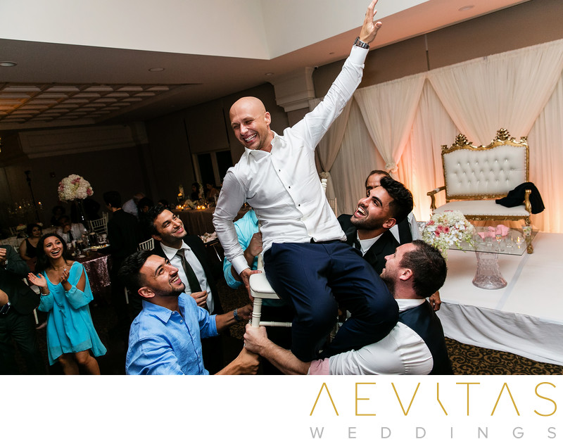 Groom on chair above dance floor at Sacramento wedding